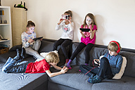 Five children on a couch using different digital devices - SARF002645