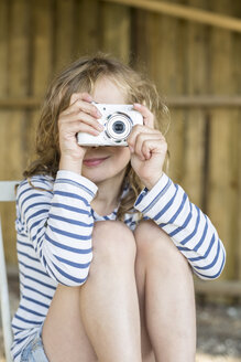 Smiling blond girl taking a picture with a digital camera - OJF000117