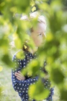 Girl seen through green leaves - OJF000120