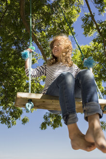 Smiling girl sitting on a swing - OJF000123