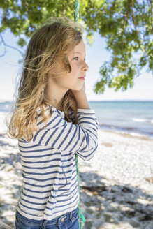 Portrait of blond girl standing on a swing on beach - OJF000126