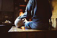 Man sitting in front of the fireplace with a soccer ball - GEMF000791