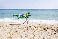 Little boy running with Brazilian flag on a beach - VABF000366