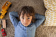 Portrait of little boy lying on carpet with toy cars besides him - VABF000369
