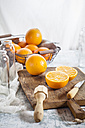 Whole and sliced orange, juice squeezer and knife on wooden board - SBDF002782