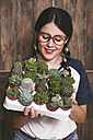 Hipster young woman with tray cacti and succulents - RTBF000004