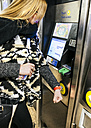 Young woman paying with her smartwatch on the subway - MGOF001537