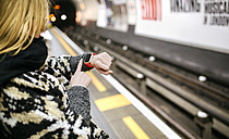 Young woman looking on her smartwatch waiting for the subway - MGOF001540