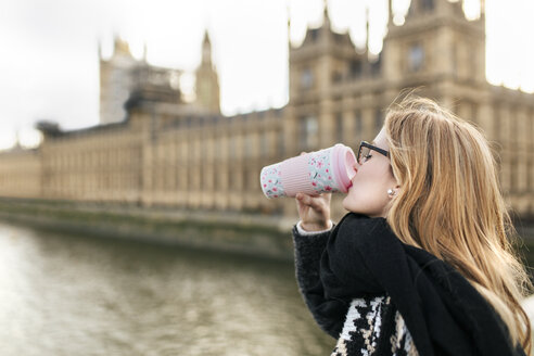 UK, London, young woman drinking coffee in front of Palace of Westminster - MGOF001546