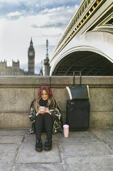 UK, London, young woman listening music near Westminster Bridge - MGOF001552