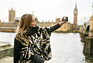 UK, London, young woman taking a selfie near Westminster Bridge - MGOF001558