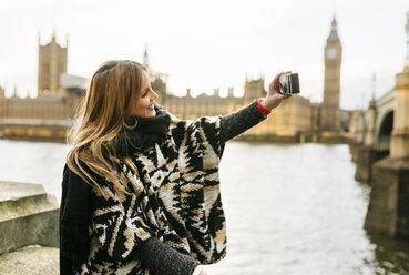 UK, London, young woman taking a selfie near Westminster Bridge - MGOF001558