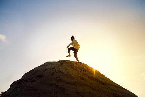 Man with bun running uphill - BMAF000094
