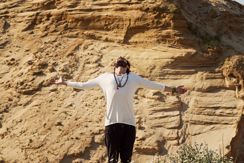 Man with arms outstretched in front of rock - BMAF000100