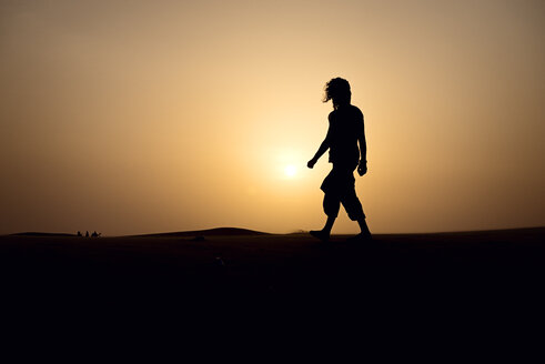 Silhouette of man walking on dune - BMAF000127