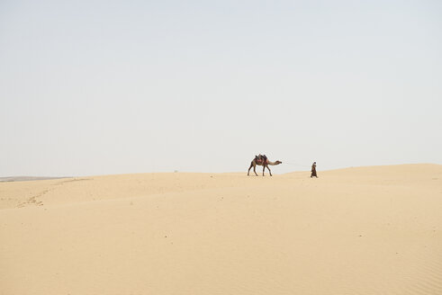 Man leading camel through desert - BMA000136