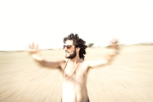 Bare chested man with sunglasses reaching out in desert - BMAF000148