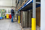 Man examining machine block in storehouse - DIGF000050