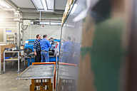 Two men in factory talking at eroding machine - DIGF000083