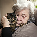 Portrait of senior woman cuddling with her cat - MIDF000719
