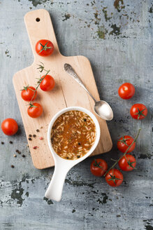 Bowl of tomato soup and rice on chopping board - MYF001405