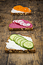 Three wholemeal bread slices with different spreads and toppings on wood - LVF004665