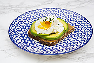 Wholemeal bread slices with sliced avocado and poached eggs on plate - LVF004671