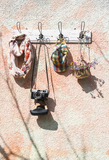 Sping items and old camera on wall coat rack - DEGF000753