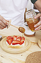 Young man putting honey on toast with strawberries - RTBF000020