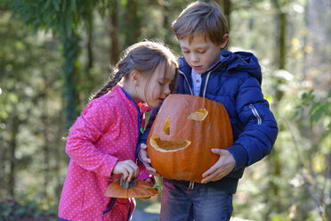Boy and girl examining Halloween pumpkin in forest - LBF001418