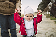 Toddler learning to walk hand in hand with two women - RAEF000948