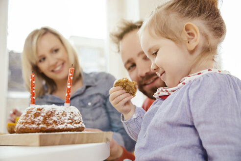Little girl having a piece of her carrot birthday cake while parents watching - MFF002883