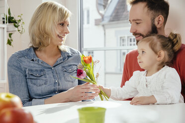 Little girl giving her mother flowers while father is watching - MFF002889