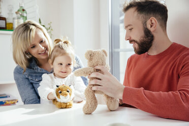 Mother and daughter playing with plush tiger to communicate with plush bear played by father - MFF002892