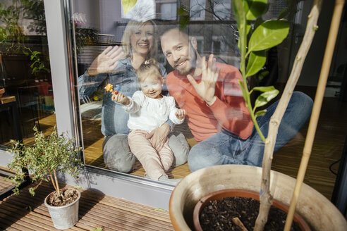 Mother, father and little girl waving out of window - MFF002895