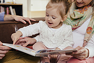 Parents reading book to little girl - MFF002898