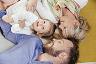 Family of three lying down on carpet at home - MFF002901