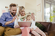 Parents and little daughter skyping with digital tablet at home - MFF002913