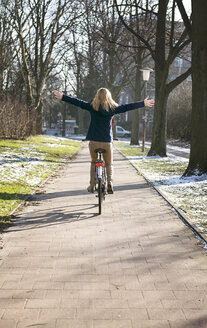 Blond woman riding bike with arms outstretched - BMA000160
