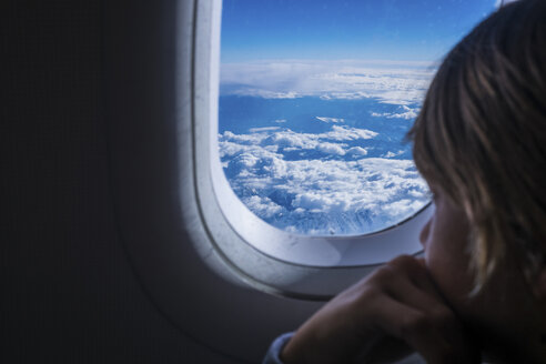 Boy looking out of airplane window - SIPF000254