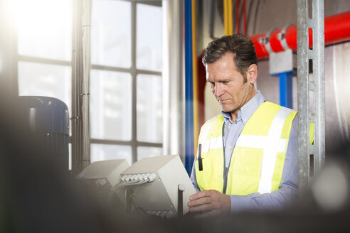 Man wearing reflective vest looking at device in industrial plant - FKF001724