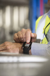 Man using smartwatch in industrial plant - FKF001727