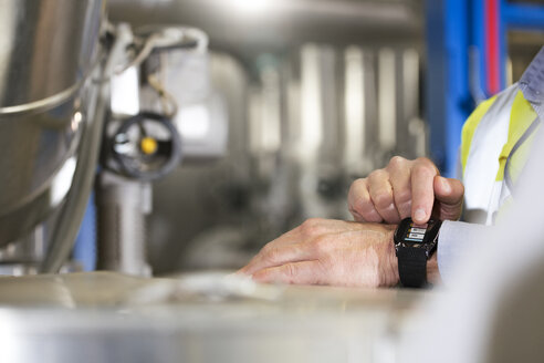 Man using smartwatch in industrial plant - FKF001730