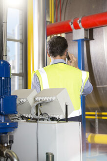 Man wearing reflective vest telephoning in industrial plant - FKF001733