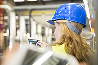 Woman wearing reflective vest controlling industrial plant with digital tablet - FKF001736