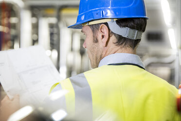 Man wearing reflective vest looking at paper in industrial plant - FKF001742