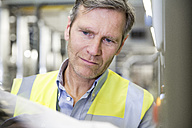 Man wearing reflective vest in industrial plant - FKF001745