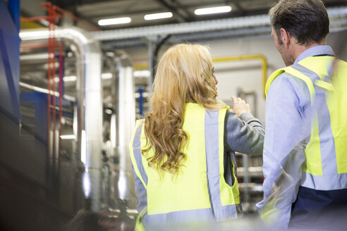 Colleagues wearing reflective vests talking in industrial plant - FKF001748