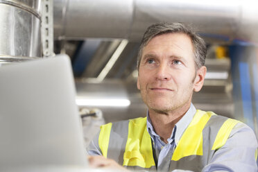 Man wearing reflective vest using laptop in industrial plant - FKF001754