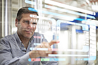 Man using transparent touchscreen device - FKF001760